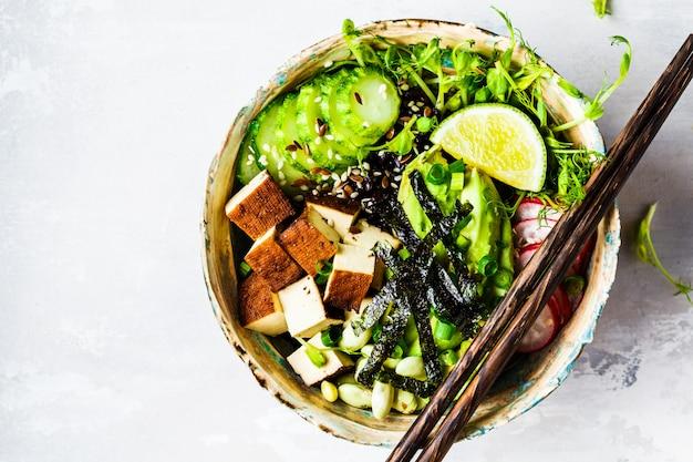 Ciotola poke con avocado, riso nero, tofu affumicato, fagioli, verdure, germogli Foto Premium