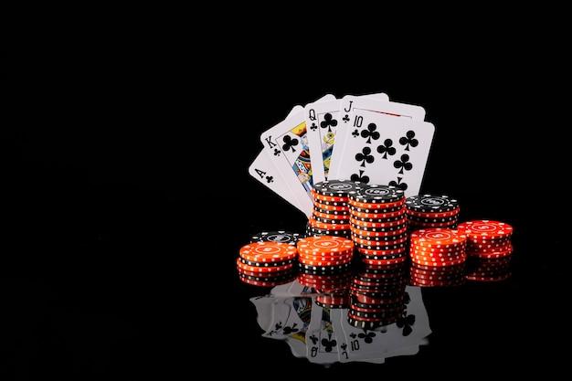 Poker chips e royal flush club su sfondo nero riflettente Foto Premium
