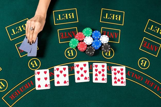 Gioca a poker. chip nella mano di un giocatore. vista dall'alto. la mano femminile alza le carte per vedere Foto Premium