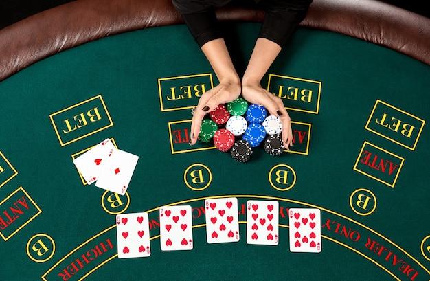 Gioca a poker. chip nella mano di un giocatore. vista dall'alto. il giocatore punta all-in. le mani delle donne stanno muovendo le fiches Foto Premium
