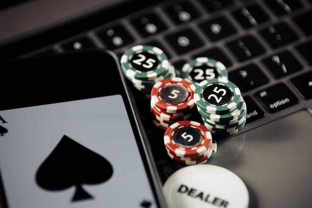 Concetto di gioco online di poker. fiches da poker, carte da gioco e smartphone sulla tastiera Foto Premium