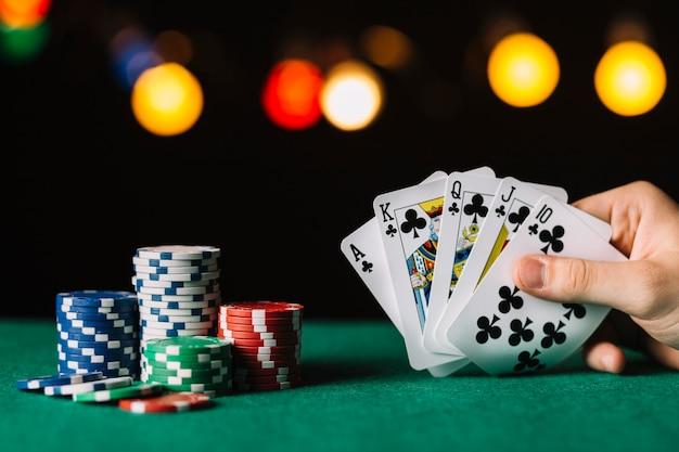 La mano del giocatore di poker con il club di rossoreare vicino a chip sulla superficie verde Foto Premium