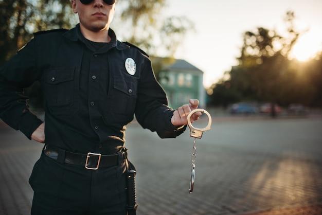 L'ufficiale di polizia tiene le manette nelle mani Foto Premium