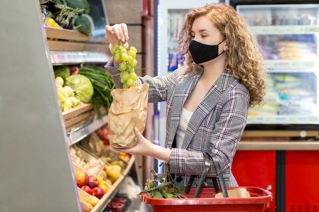 Poman con maschera al mercato dello shopping Foto Premium