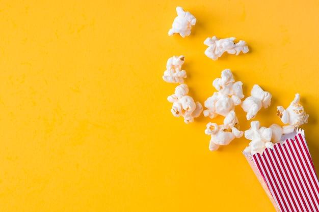 Popcorn su sfondo giallo con spazio di copia Foto Premium