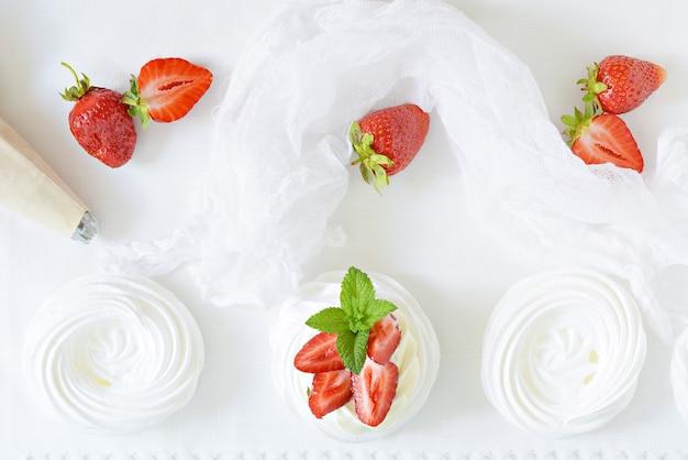 Porzione dessert australiano pavlova con crema al burro ariosa, fragole fresche e menta su un piatto bianco. Foto Premium
