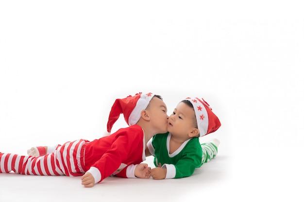 Il ragazzo asiatico del ritratto bacia il suo fratello felice su bianco Foto Premium