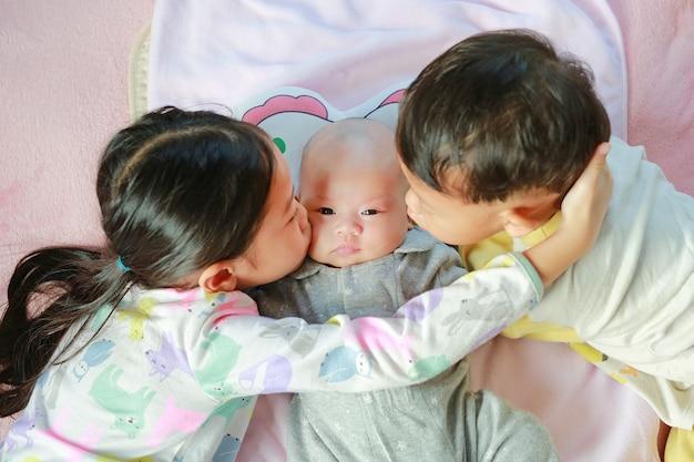Ritratto della bambina asiatica del bambino e del suo fratellino che baciano la sua sorella appena nata sdraiata sul letto Foto Premium