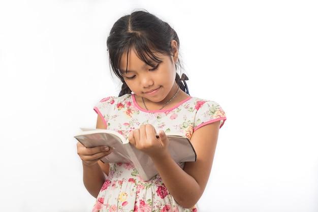 Ritratto della bambina asiatica che tiene un libro su bianco Foto Premium