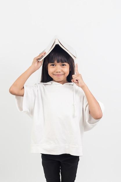 Il ritratto della bambina asiatica ha messo il libro sulla testa. Foto Premium