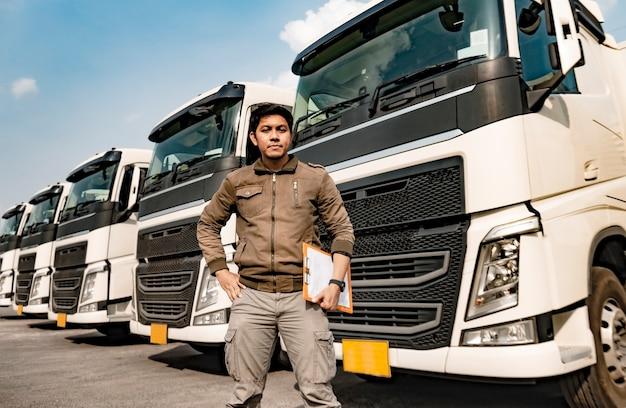 Ritratto della lavagna per appunti asiatica della tenuta dell'autista di camion che ispeziona la lista di controllo di manutenzione del veicolo di sicurezza un camion dei semi Foto Premium
