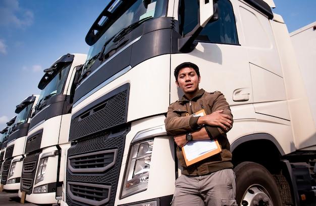 Ritratto dell'autista di camion asiatico che sta con il camion moderno dei semi Foto Premium