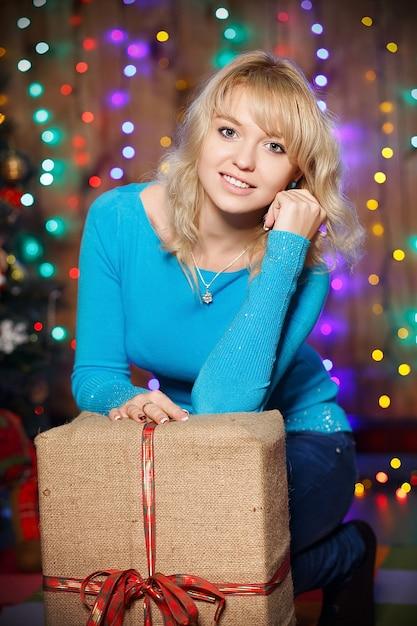 Ritratto di attraente giovane femmina affascinante bionda con un grande regalo all'interno della scatola con decorazioni natalizie Foto Premium
