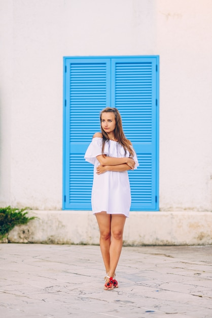 Ritratto di bella ragazza affascinante in un abito bianco su persiane in legno blu alle finestre Foto Premium