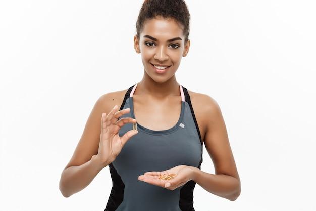 Ritratto di bella donna felice afroamericana che prende pillola. Foto Premium