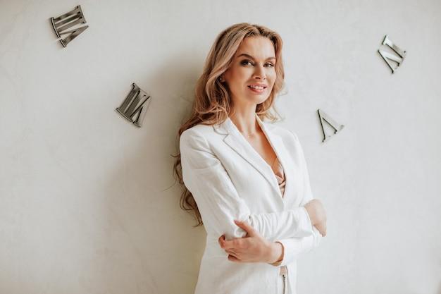 Ritratto di bella donna dai capelli lunghi in giacca da ufficio bianca in posa con le braccia incrociate vicino al muro bianco con orologi. Foto Premium