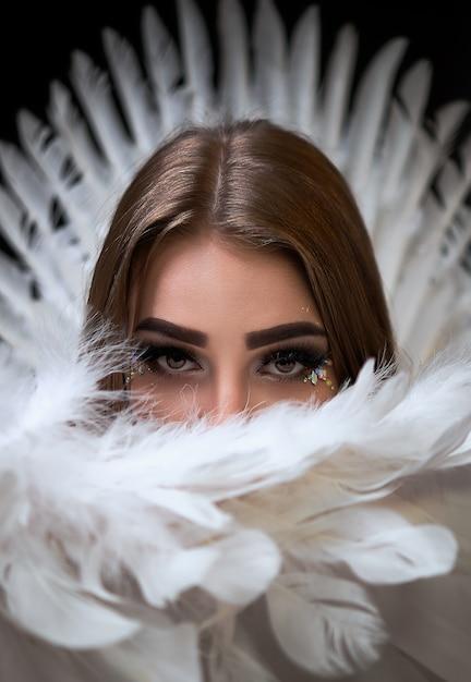 Ritratto di una bellissima modella con ali bianche. lo sfondo è nero Foto Premium