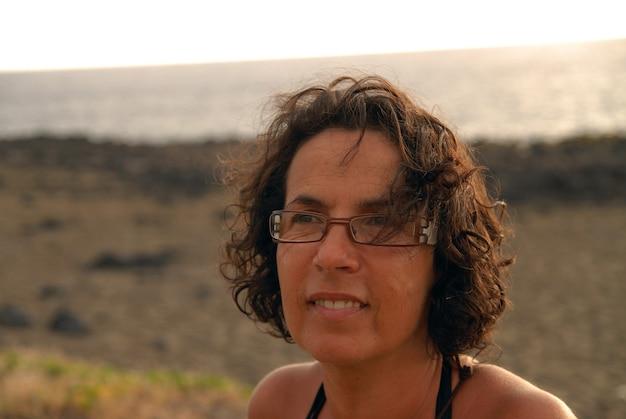 Ritratto di bella bruna matura abbronzata con gli occhiali Foto Premium