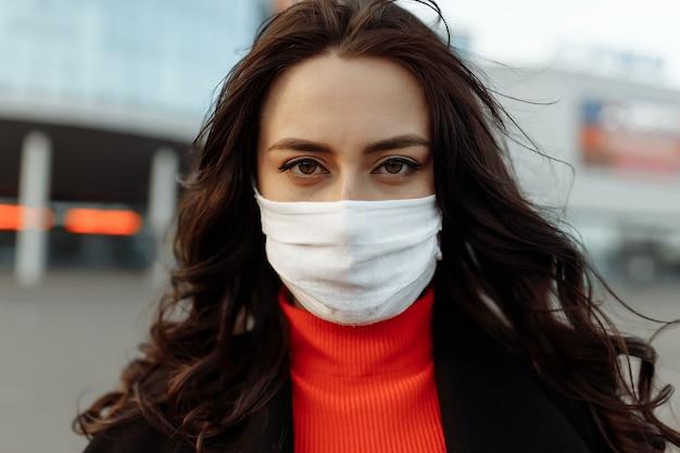 Ritratto di bella donna che cammina per strada indossando maschera protettiva come protezione contro le malattie infettive. modello attraente infelice con influenza all'aperto. Foto Premium