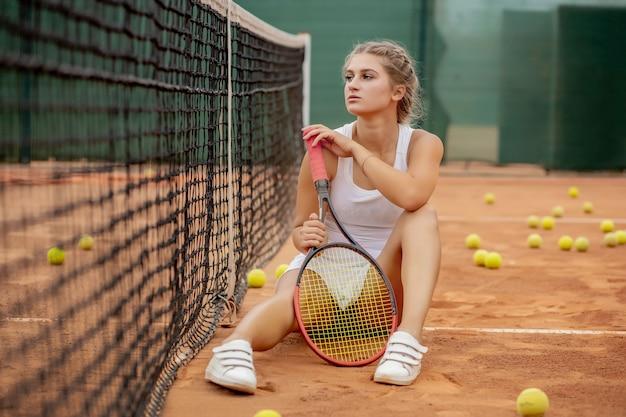 Ritratto di giovane e bella donna seduta vicino a rete nel campo da tennis con palla all'aperto. Foto Premium