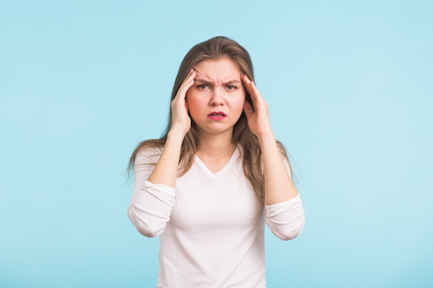 Ritratto di bella giovane donna con le spalle nude che tocca le sue tempie sensazione di stress, sull'azzurro Foto Premium