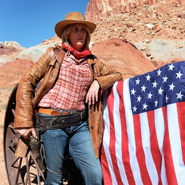 Ritratto di una cowgirl bionda con la bandiera americana Foto Premium