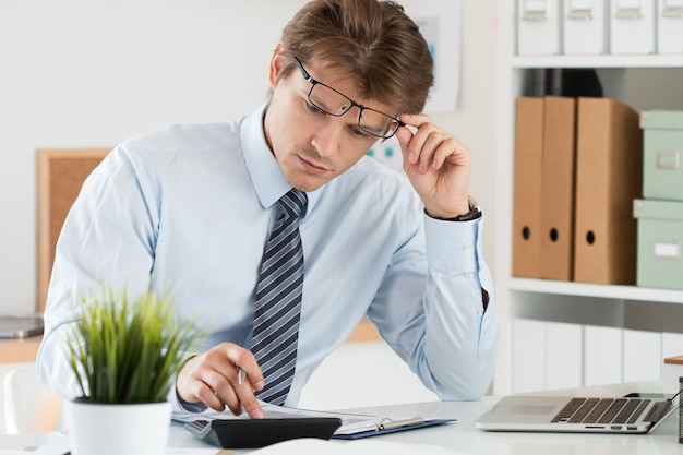 Ritratto di contabile o ispettore finanziario che adegua i suoi occhiali facendo rapporto, calcolando o controllando l'equilibrio. finanze domestiche, investimenti, economia, risparmio di denaro o concetto di assicurazione Foto Premium