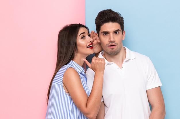 Ritratto di donna castana che bisbiglia pettegolezzi segreti o interessanti all'uomo eccitato nel suo orecchio, isolato sopra la parete colorata Foto Premium