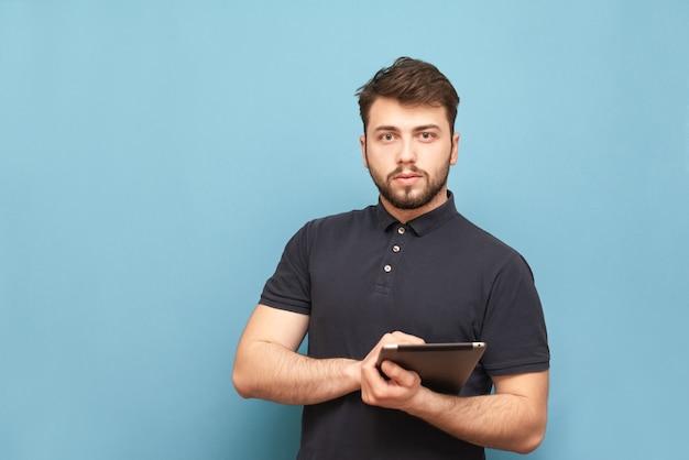 Ritratto di un uomo d'affari con la barba in piedi sul blu con una tavoletta in mano, indossa una maglietta Foto Premium