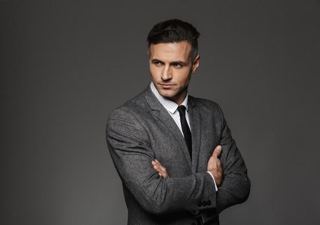 Ritratto di uomo d'affari che indossa il costume formale in piedi con le braccia incrociate e guardando da parte, isolato sopra il muro grigio Foto Premium