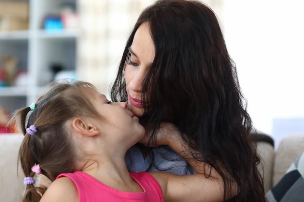 Ritratto di mamma premurosa e bambino felice che gode di trascorrere del tempo divertente insieme a casa. madre adorabile che bacia figlia felice. concetto di infanzia e genitorialità Foto Premium