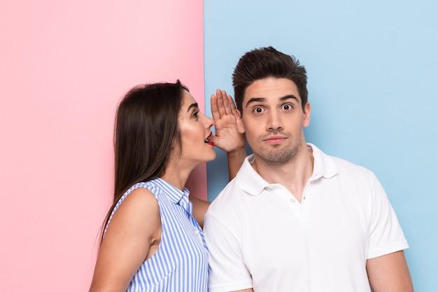 Ritratto di donna caucasica che bisbiglia pettegolezzi segreti o interessanti all'uomo curioso nel suo orecchio, isolato sopra la parete colorata Foto Premium