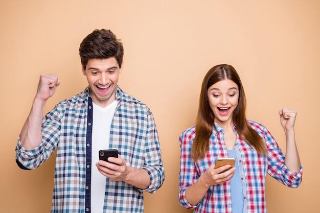 Ritratto di allegro eccitato sposato due persone utilizzano smartphone ricevi notifiche sui social media sulla vincita della lotteria urlare wow sì alzare i pugni indossare camicia a quadri isolato su sfondo di colore pastello Foto Premium