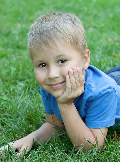 Ritratto di un bambino sdraiato sull'erba Foto Premium