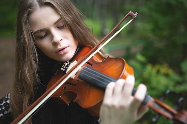 Ritratto ravvicinato di una bella ragazza violinista che ha abbassato gli occhi con entusiasmo suonando il violino romantico Foto Premium