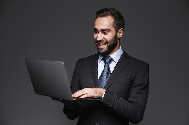 Ritratto di un uomo d'affari bello fiducioso che indossa tuta isolata, tenendo il computer portatile Foto Premium
