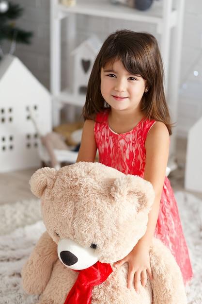 Ritratto di una piccola ragazza sveglia del brunette che abbraccia un grande orsacchiotto molle all'interno con le decorazioni di natale Foto Premium