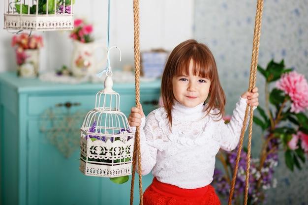 Ritratto di una bambina carina cavalca su un'altalena all'interno con decorazioni shabby chic Foto Premium