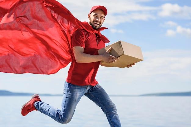 Ritratto del fattorino che indossa il mantello da supereroe Foto Premium