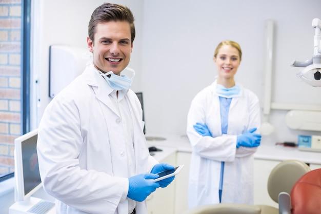 Ritratto del dentista che tiene compressa digitale con il suo collega Foto Premium