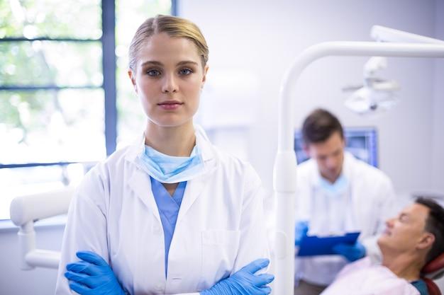 Ritratto di dentista in piedi con le braccia incrociate Foto Premium