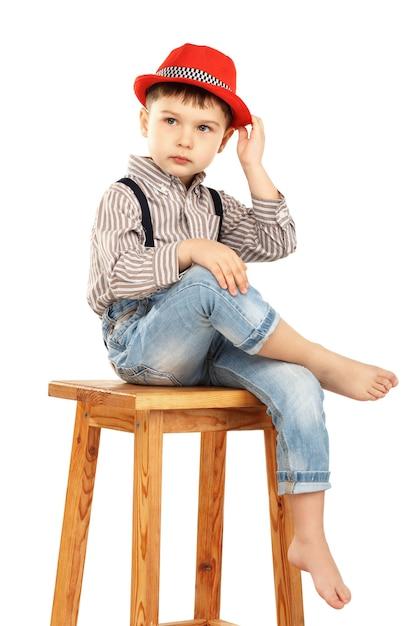 Ritratto di un ragazzino divertente seduto su uno sgabello alto in un cappello rosso isolato su bianco Foto Premium