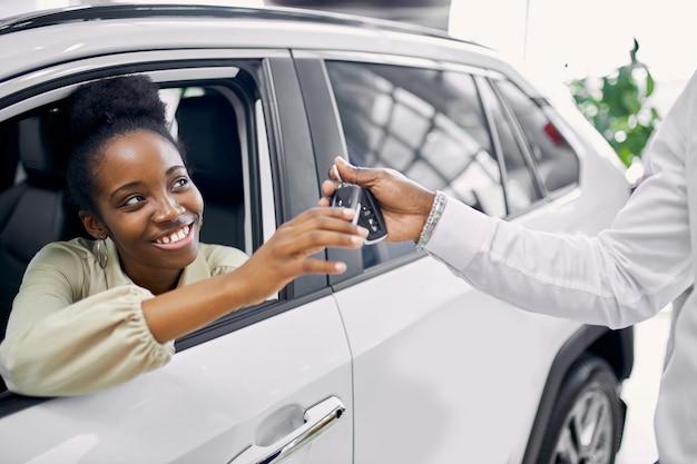 Ritratto di bella signora afro che ottiene le chiavi in macchina Foto Premium
