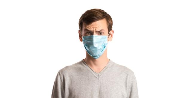 Ritratto di un ragazzo in una maschera usa e getta su un bianco Foto Premium