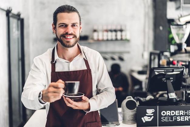 Ritratto del barista barbuto bello uomo piccolo imprenditore sorridente e che tiene tazza di caffè nel bar o caffetteria. barista maschio in piedi al caffè Foto Premium