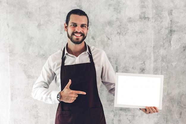 Ritratto del barista barbuto bello uomo piccolo imprenditore che sorride e che tiene la struttura di legno del bordo vuoto con lo spazio in bianco bianco in un caffè Foto Premium