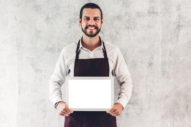 Ritratto del barista barbuto bello uomo piccolo imprenditore sorridente e in possesso di bordo di legno vuota cornice con mockup bianco vuoto in un caffè Foto Premium