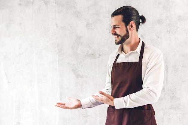 Ritratto del piccolo imprenditore barbuto bello barista che sorride sul fondo della parete Foto Premium