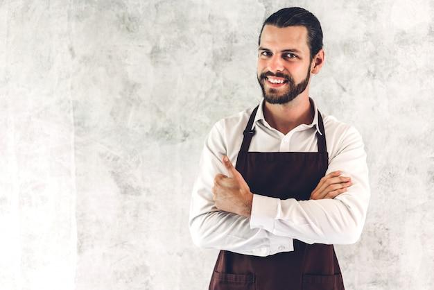 Ritratto di bello barbuto barista uomo piccolo imprenditore sorridente sulla parete della parete Foto Premium