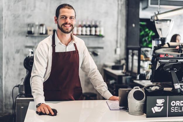 Ritratto di bello barbuto barista uomo piccolo imprenditore che lavora dietro il bancone in un bar Foto Premium